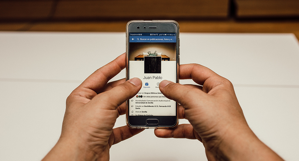 A person holds phone with Facebook app open